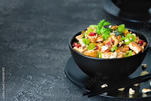 Photo  Stir fried tofu, cashew, chili on dark background. Copy space