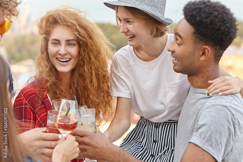 Fotografía  Group of mixed race friends raising drinks for cheers celebration, embracing each other, celebrating birthday of their friend