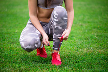 Girl Athlete Tying Shoes Before Exercise Closeup