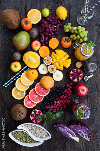 Fototapety, obrazy: Fruits and frozen berries on dark rustic wooden table. Purple and yellow smoothie bowl formula. Clean eating concept. Various green and red veggies, fruit and superfoods ready to prepare smoothie bowl