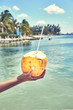 Fresh coconut drink directly from the fruit / Hand of black woman holding coconut with drinking straw at caribbean coast