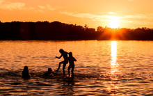 Kids And Families Are Having Fun At A Lake Under Sunset