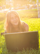 Young woman using laptop in the park lying on the green grass. Leisure time activity concept
