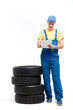 Service worker with notebook against pile of tires