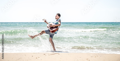 Magasin de musique young man with acoustic guitar on the beach