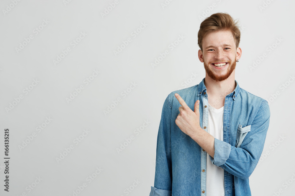 Fototapeta Portrait of cheerful young man smiling looking at camera pointing finger up over white background.