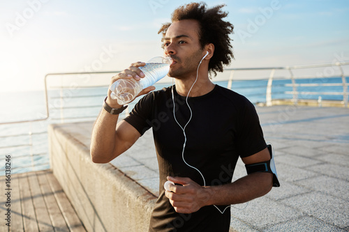 Tablou Canvas Fit afro-american male athlete drinking water out of plastic bottle after jogging on the pear in the morning