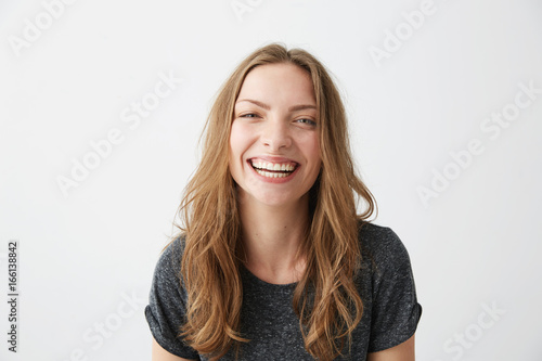 Fotografia  Young cheerful happy girl smiling laughing looking at camera over white background