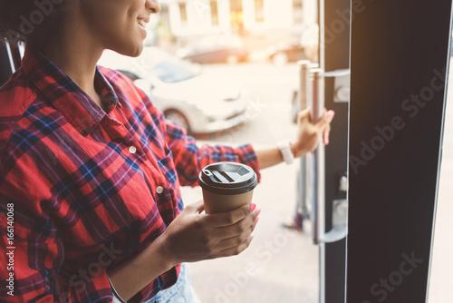 Photo  Cheerful girl is holding coffee
