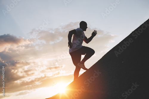 Fotografie, Obraz  Male runner trains in an ascent to a mountain