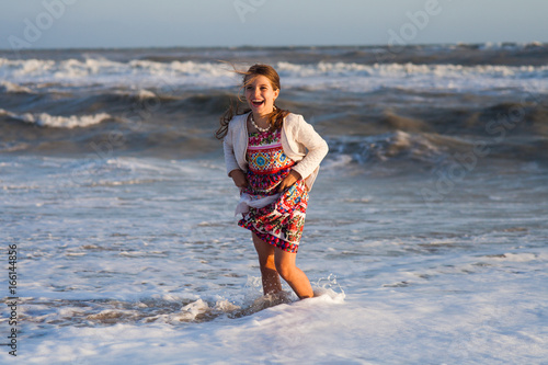 Fototapeta girl in a skirt playing on the sandy shore before a stormy sea