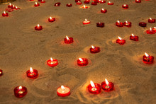 Lit Candles On Sand In A Churc...