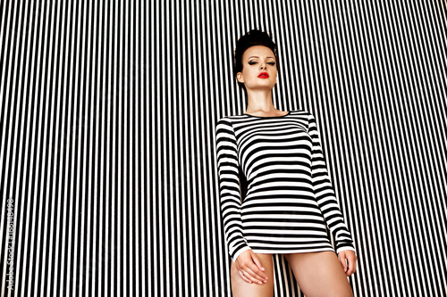 Obraz na plátně  Sexy and beautiful woman in striped dress on striped background