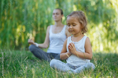 Young mother and cute little daughter meditating in lotus pose together