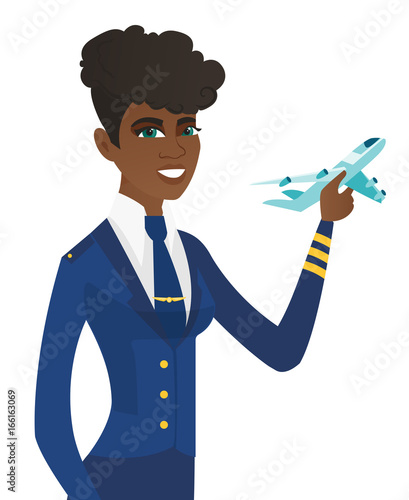 Photo Young african stewardess with model of airplane.
