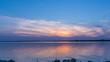 Timelapse of a beautiful sunset on a lake. In the end, the sun hides behind the horizon.