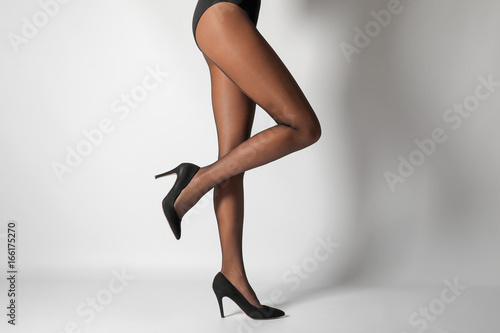 Photographie  Legs of beautiful young woman in black tights on light background