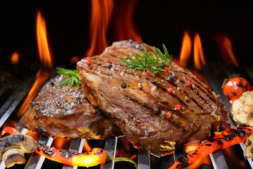 Fototapeta Do steakhouse Grilled beef steak with vegetable on the flaming grill
