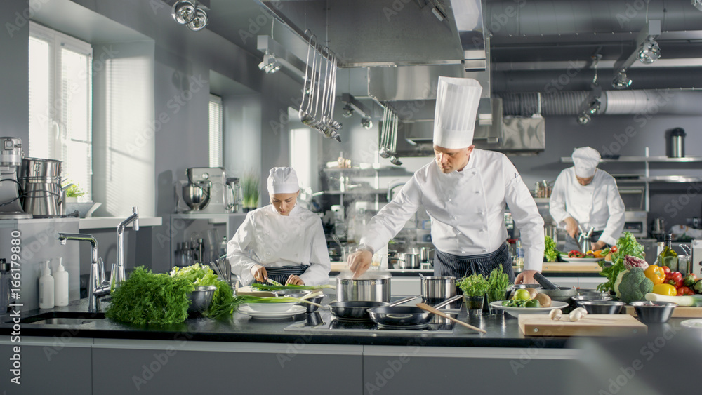 Fototapety, obrazy: Famous Chef Works in a Big Restaurant Kitchen with His Help. Kitchen is Full of Food, Vegetables and Boiling Dishes.