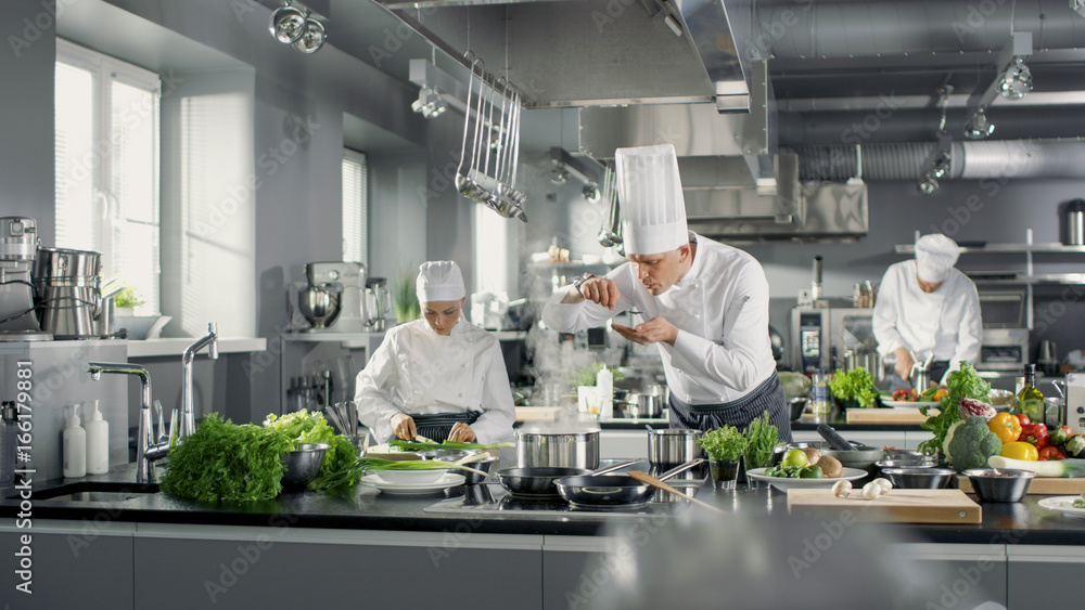 Fototapety, obrazy: Famous Chef Works in a Big Restaurant Kitchen with His Help. Kitchen is Full of Food, Vegetables and Boiling Dishes. He is trying taste.