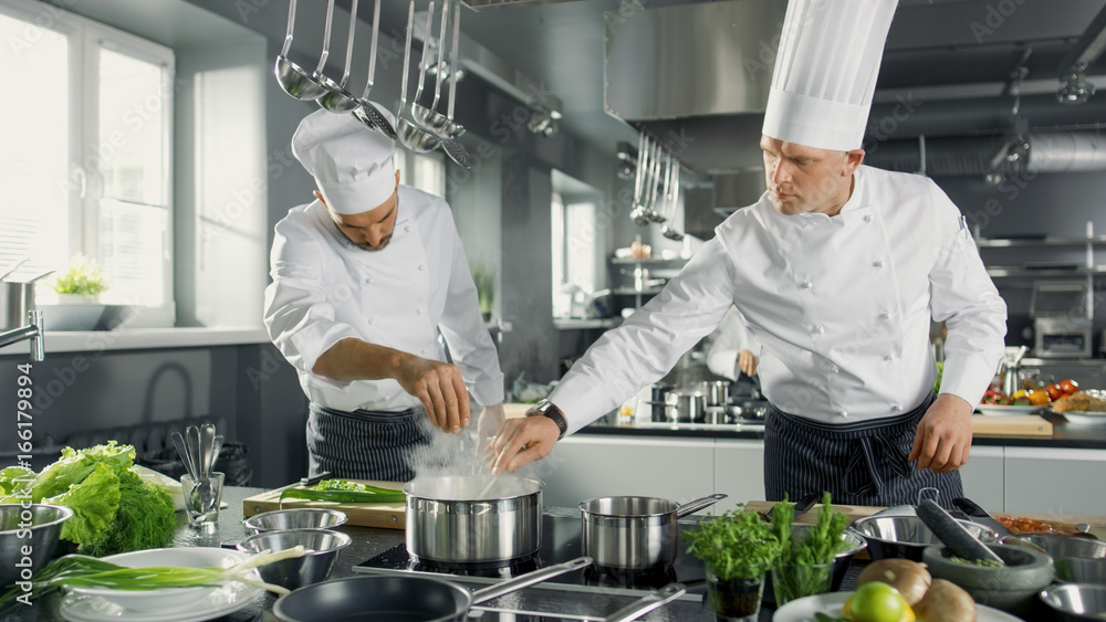 Fototapety, obrazy: Two Famous Chefs Work as a Team in a Big Restaurant Kitchen. Vegetables and Ingredients are Everywhere, Kitchen Looks Modern with Lots of Stainless Steel.
