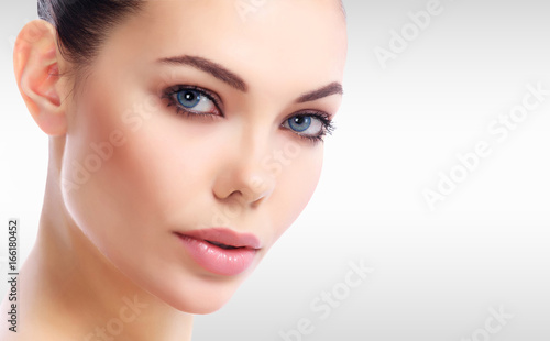 Fototapety, obrazy: Pretty woman's face against a grey background with copyspace
