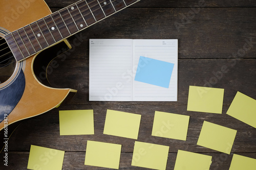 Desk of song composer for a work songwriter with a guitar and notepad on wood table Fototapet