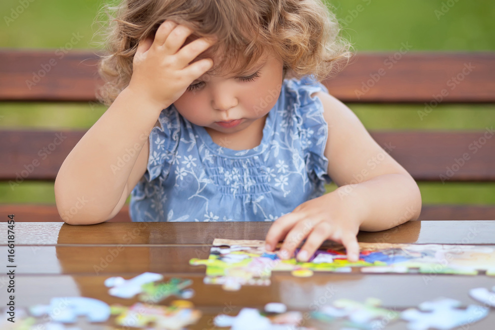 Fototapeta Difficult task. Tired child playing jigsaw with serious face.