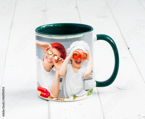 Fotografía  Big green cup with dark green handle and print of a kids cooking something