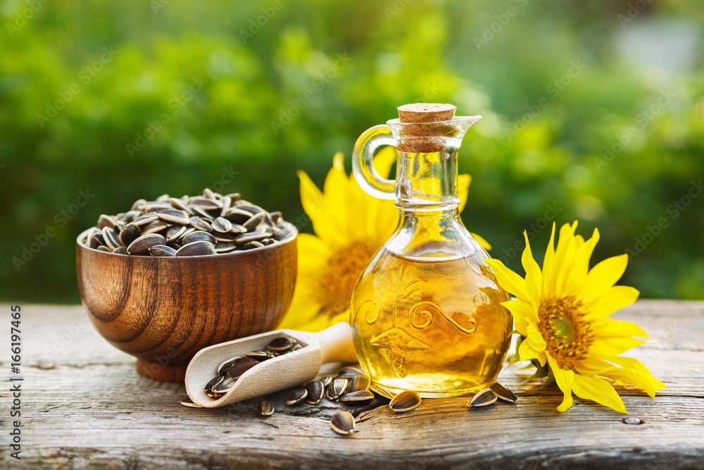 Fototapety, obrazy: Organic sunflower oil in a small glass jar with sunflower seeds and fresh flowers. Outdoors
