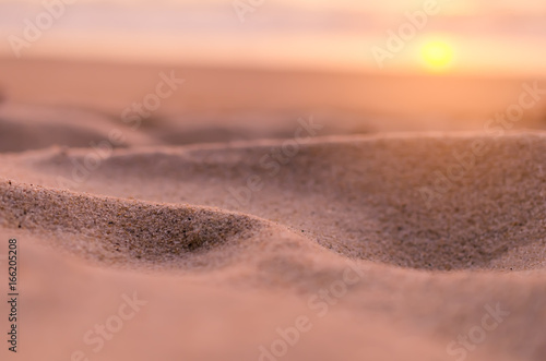 Photo Stands Salmon Blur tropical sunset beach with bokeh sun light sand abstract background.