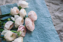 Pale Pink And White Ranunculus Bouquet On A Blue Background, On Blue And Gray Crepe Paper. Flowers. Ranunculus Asiaticus, Persian Buttercup