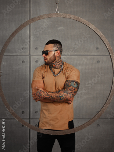 Fényképezés  Sexy closeup portrait of Elegant handsome male model with fashion tattoo and a black beard standing and posing for model tests or to journal in trend fashionable clothes