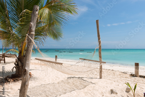 Poster Zanzibar white handmade hammock with palm tree on Zanzibar beach