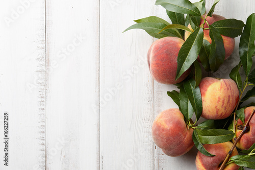 Fresh peaches fruits with leaves on wooden background, top view