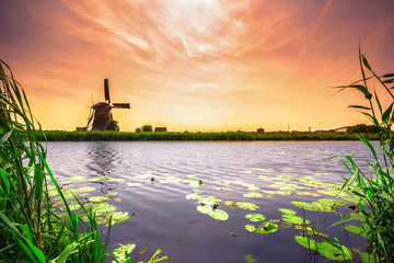 Fototapeta Vintage Traditional village with dutch windmills and river at sunset, Holland, Netherlands.
