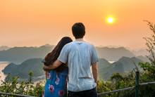Couple Enjoying Romantic Sunset At Seaside Viewpoint