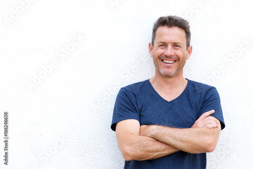 Fotografía  Close up laughing casual man standing with arms crossed