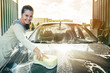 Young woman hands cleaning car by yellow sponge