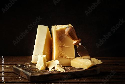 Fototapeta Parmesan cheese on wooden board. Pieces of cheese parmesan on wooden table and cheese knife. Vintage view. obraz