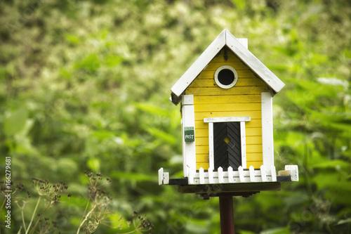 Foto Yellow birdhouse in a garden