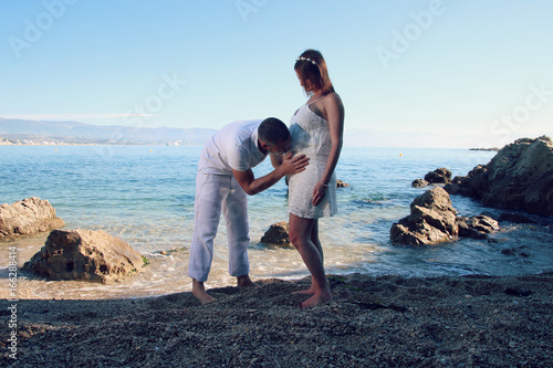 Je nomme embrassant le ventre de sa femme enceinte devant la mer Canvas Print