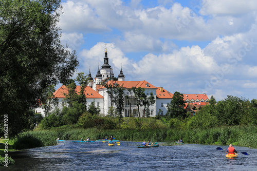Fotobehang Oude gebouw Group of people canoeing on the Narew river at the bottom of the hill with the monastic complex with defensive features from 16th and 17th century, Podlasie region, Suprasl, Poland