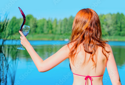 Fotografie, Obraz  Red hair young woman in swimsuit rest near blue water with glass of red wine