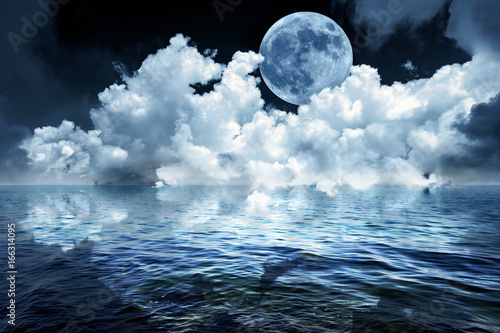 Big full moon in night sky over the ocean reflecting in calm water