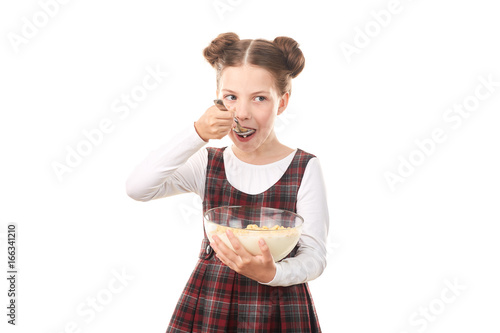 Portrait of cute girl in school uniform eating cereal with milk against white background
