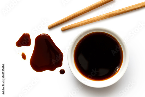 Soya sauce in white ceramic bowl on white from above with wooden chopsticks. Spilled soya sauce.