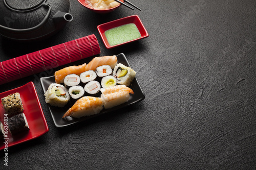Foto  Sushi set and black teapot on black table