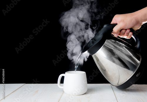 Valokuva  kettle pouring boiling water into a cup with smoke on wood table