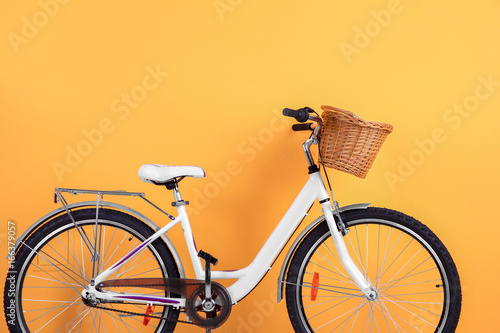 Aluminium Prints Bicycle Bicycle with empty wicker basket on color background